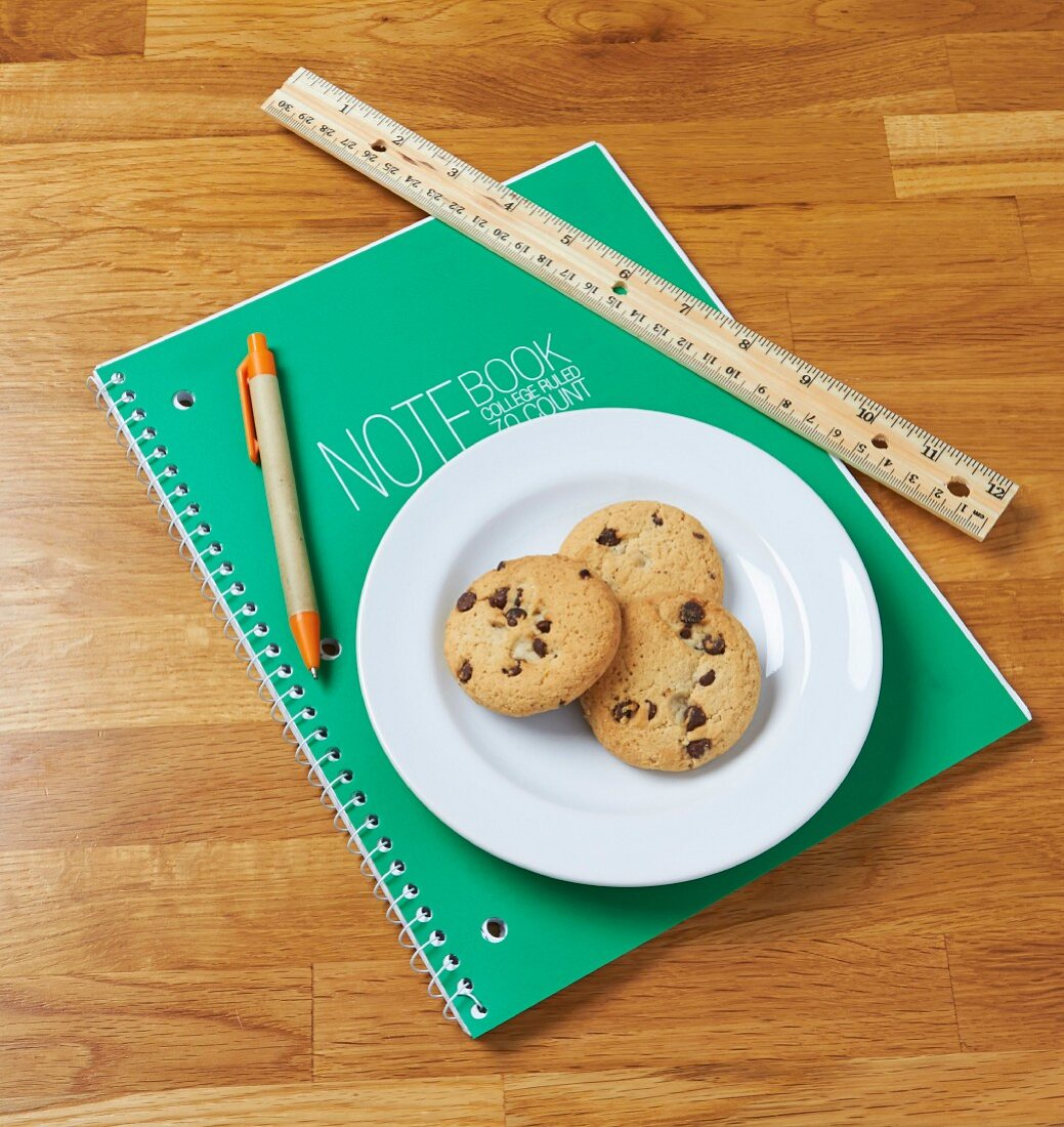 Chocolate chip cookies on a notebook with a ruler and a pencil