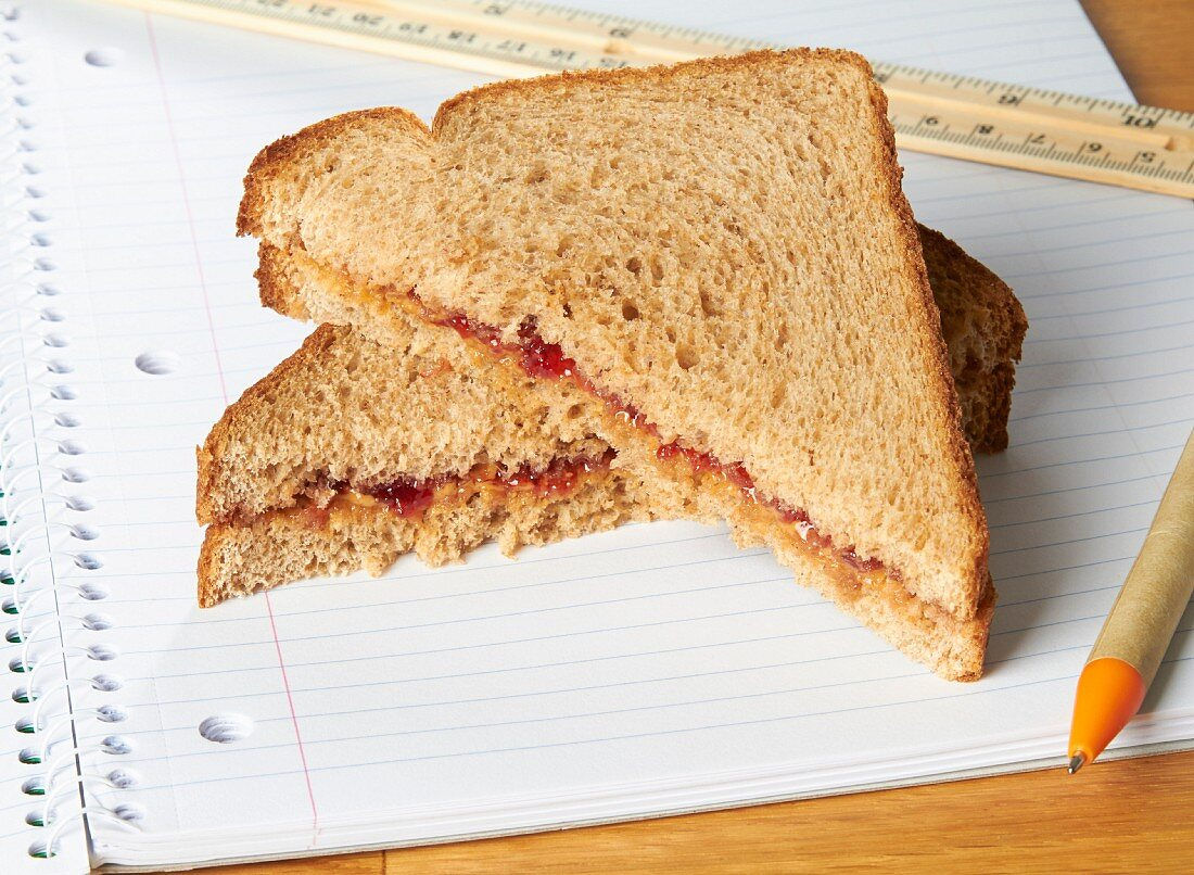 A peanut butter and jam sandwiches on a notebook