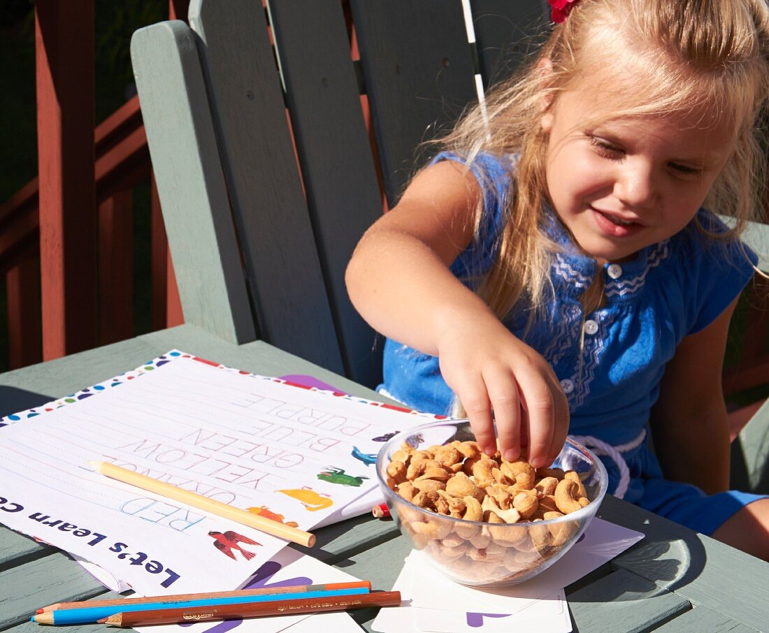 A little girl snacking on nuts while doing her homework