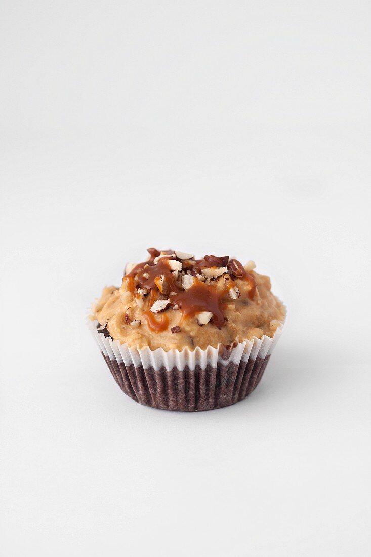 A chocolate cupcake with a caramel glaze and peanuts