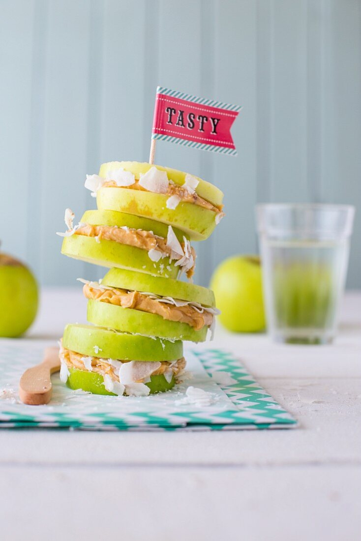A stack of nut butter and grated coconut sandwiches made with apple slices