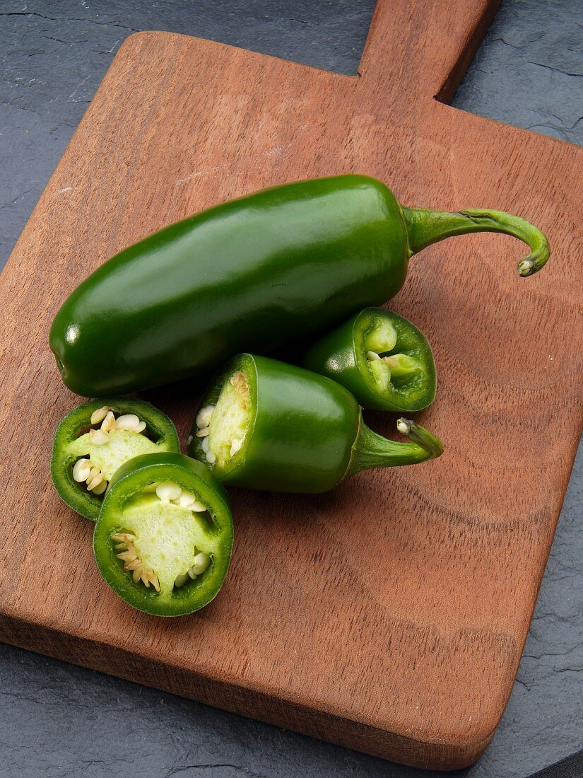 Two jalapeños, one sliced, on a chopping board