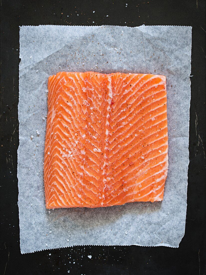 Salmon fillet seasoned with salt and sugar on a piece of paper (seen from above)