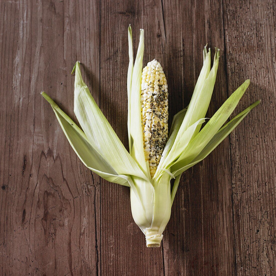 A fresh corn cob with butter and herbs, ready to cook
