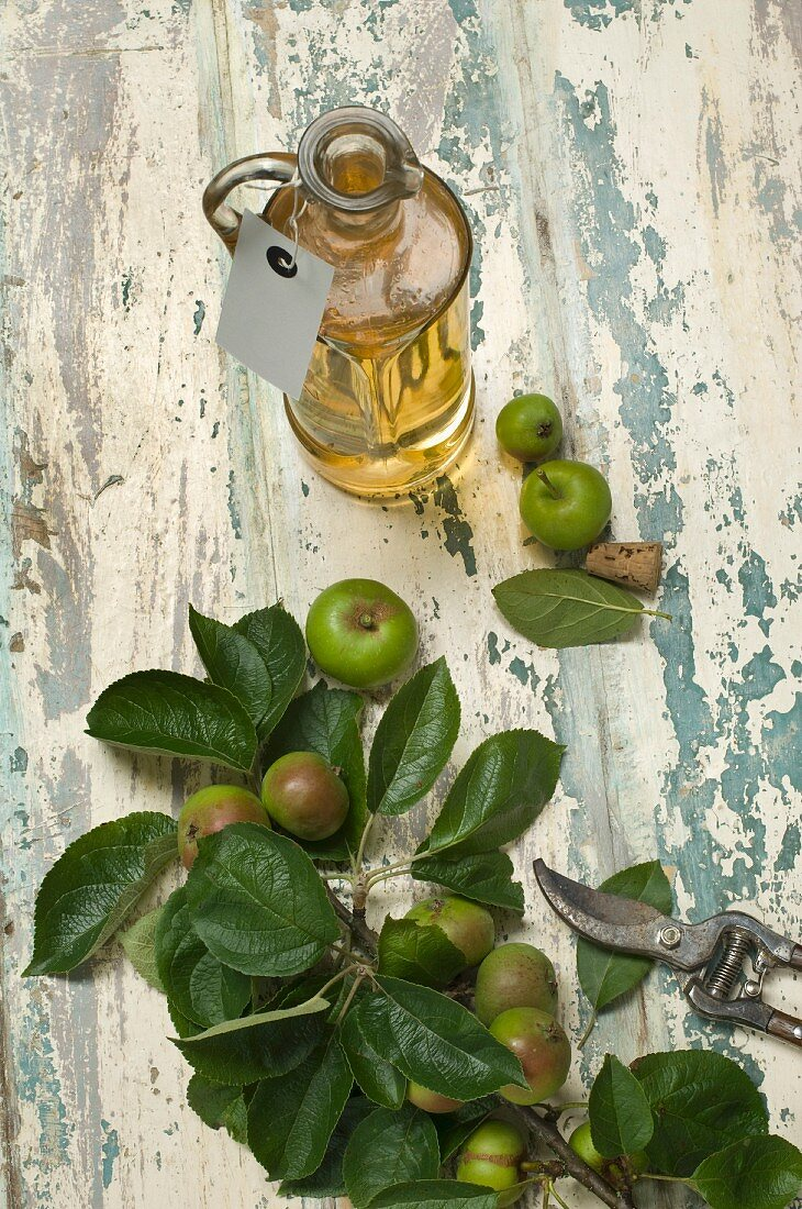 A bottle of apple vinegar and a paper label and apples on a rustic wooden surface