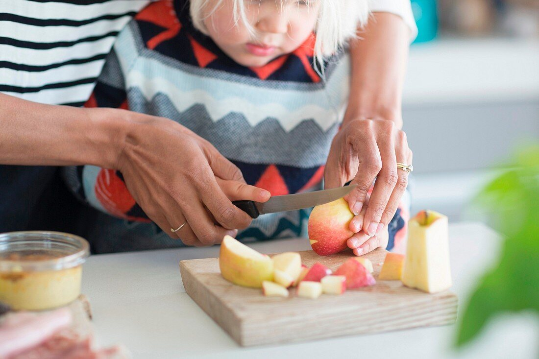 A mother helping her child to chop an apple