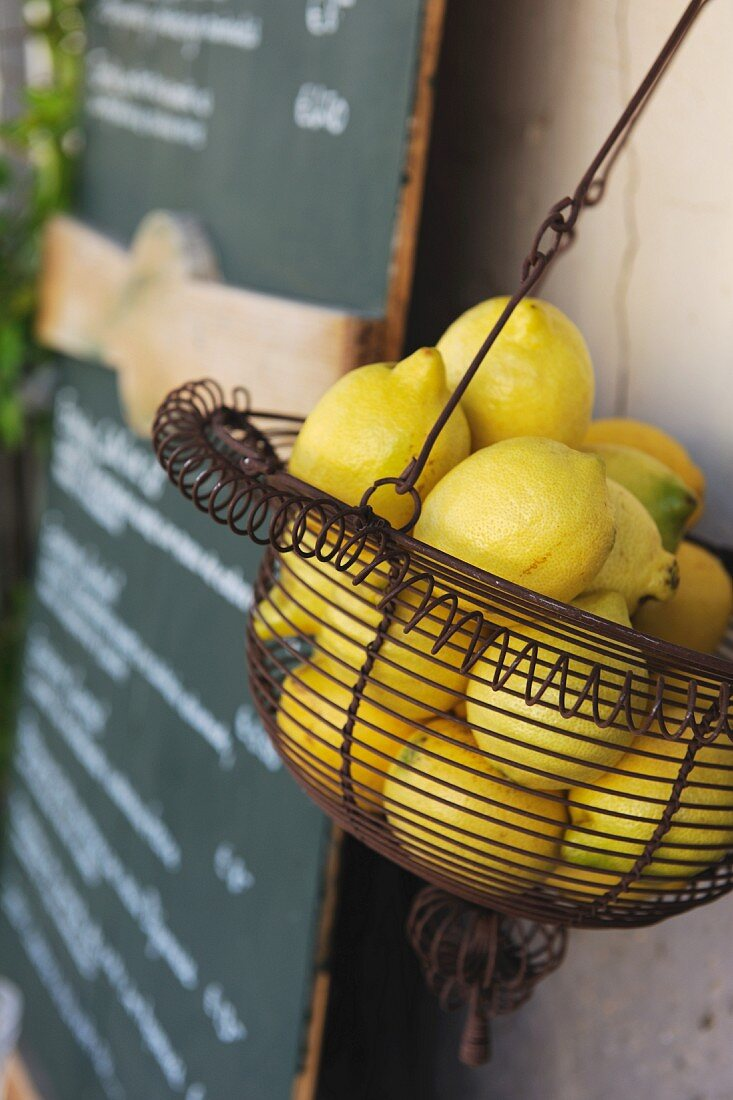 A wire basket of lemons next to a specials board in a bistro