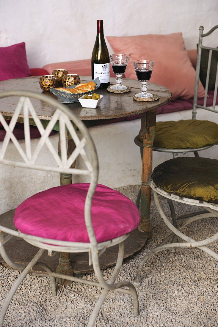 Metal bistro chairs with round seat cushions at antique wooden table set with bread and wine
