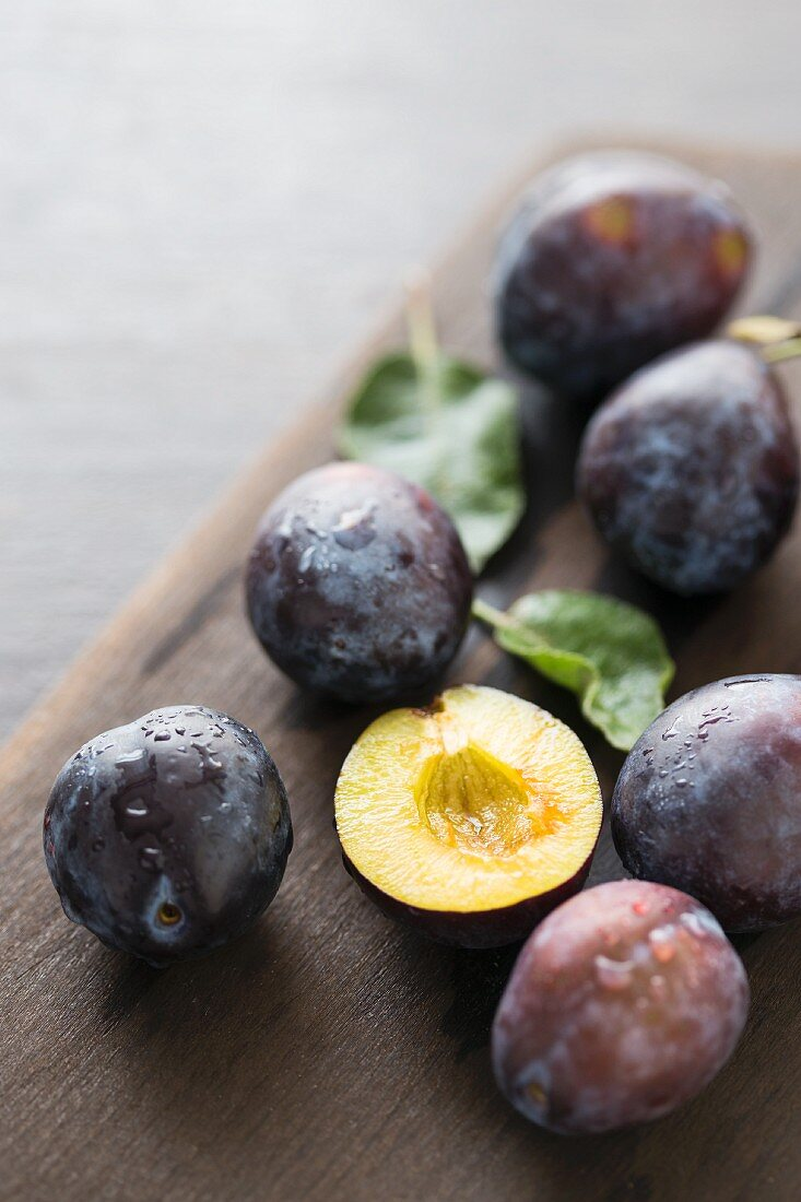 Freshly washed plums on a chopping board