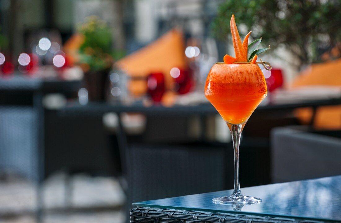 A cocktail garnish with melon carrots on a patio table (Buddha-Bar Hotel, Paris)