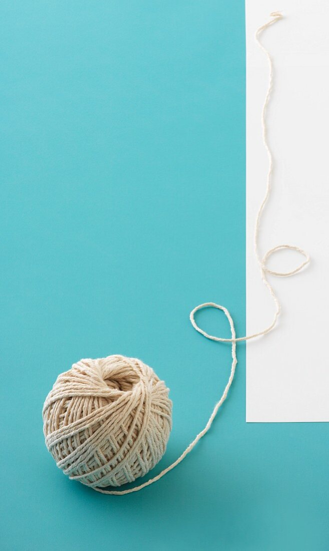 A ball of twine on a light-blue surface