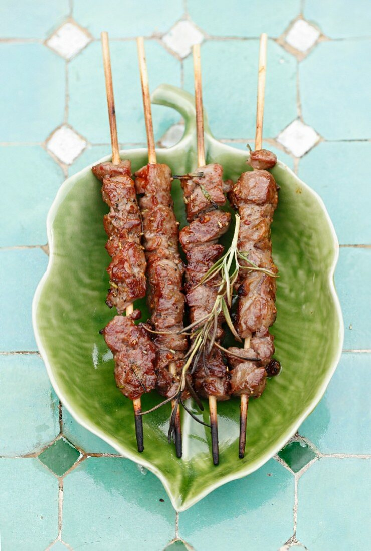 Grilled lamb skewers on a leaf-shaped plate