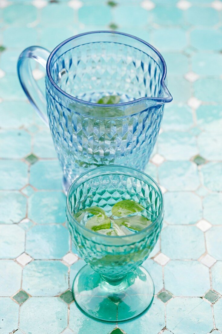 Water with mint in a blue glass carafe and a drinking glass