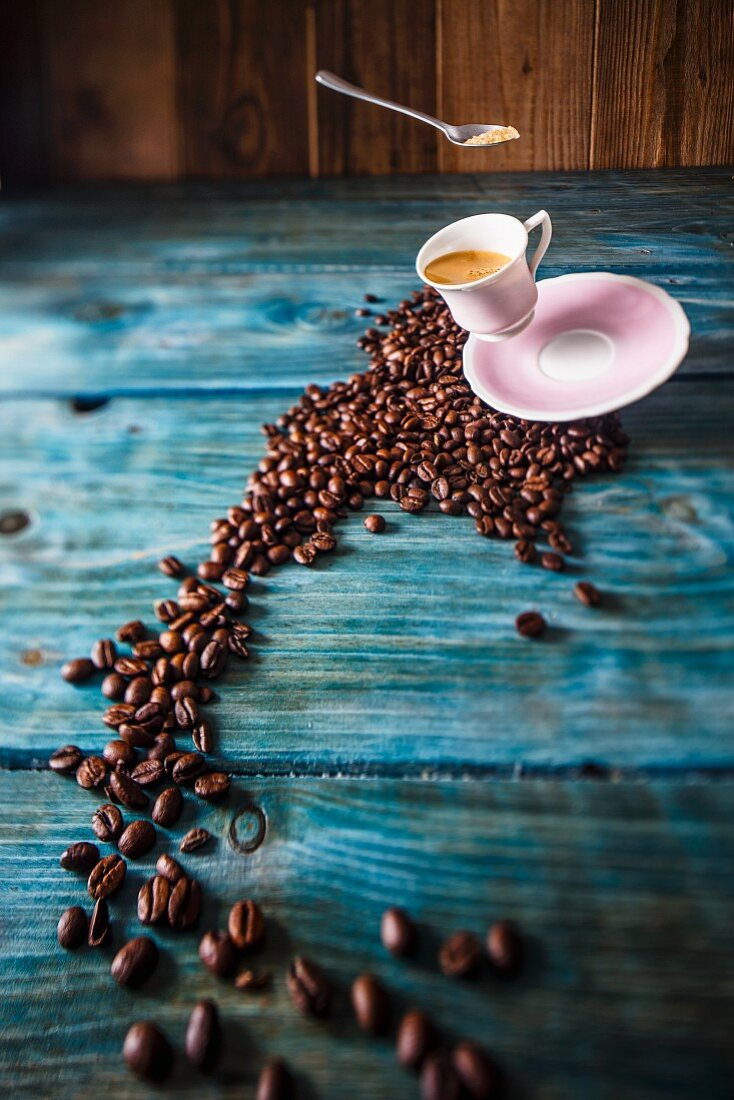 A cup of espresso flying over coffee beans on a blue wooden table
