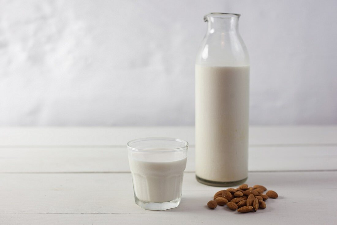 Almonds, and almond milk in a glass and in a bottle
