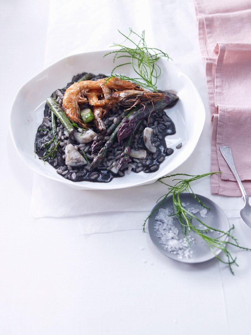 Black risotto with prawns, green asparagus and santolina
