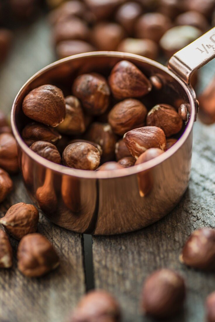 Hazelnuts in a copper cup and on a wooden surface