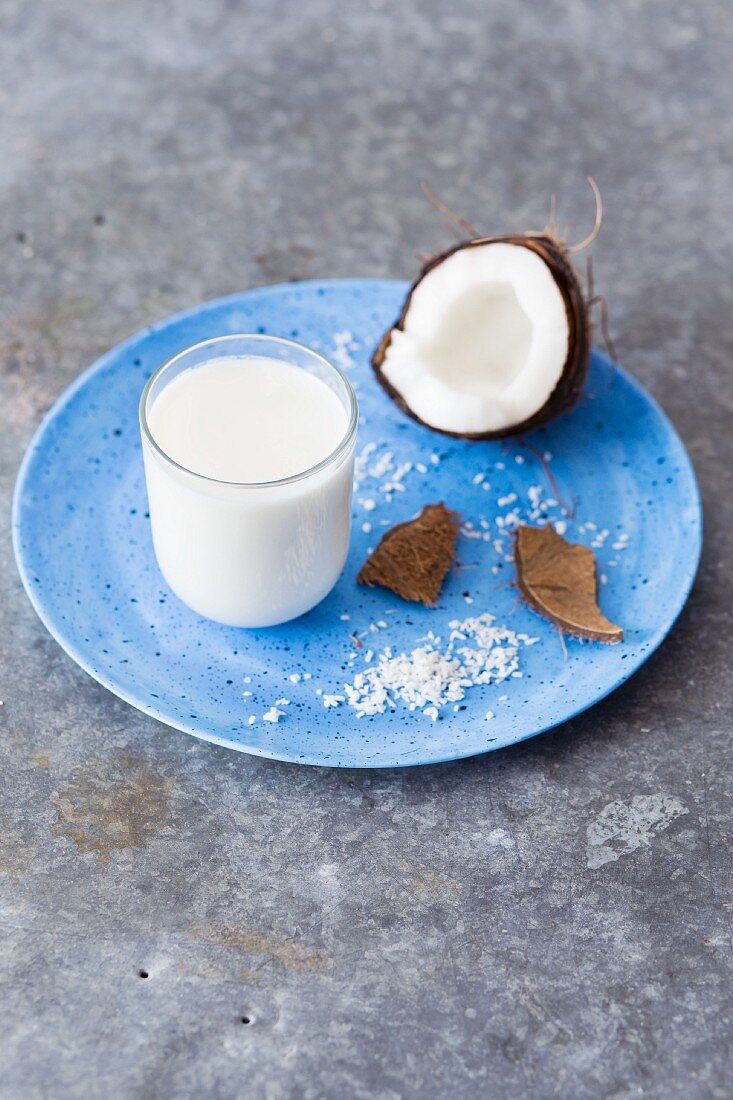 A glass of coconut milk, fresh coconut and grated coconut