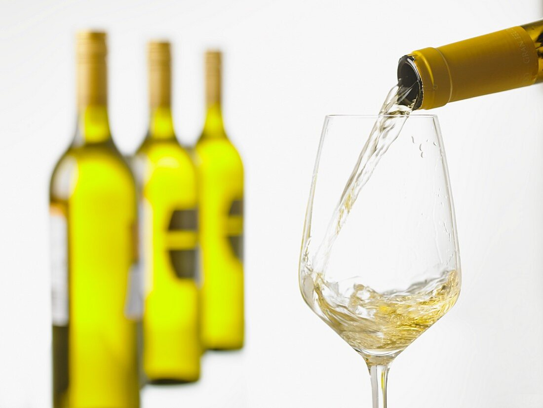 White white being poured into a glass with a row of wine bottles in the background