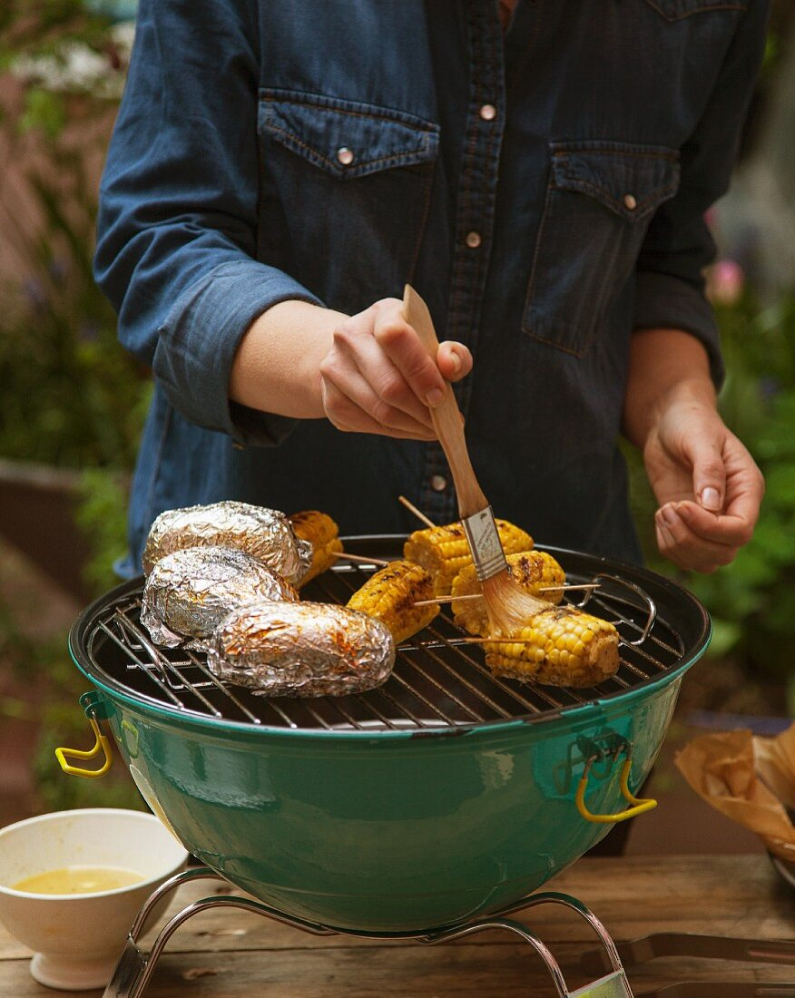 Corncobs and jacket potatoes being grilled