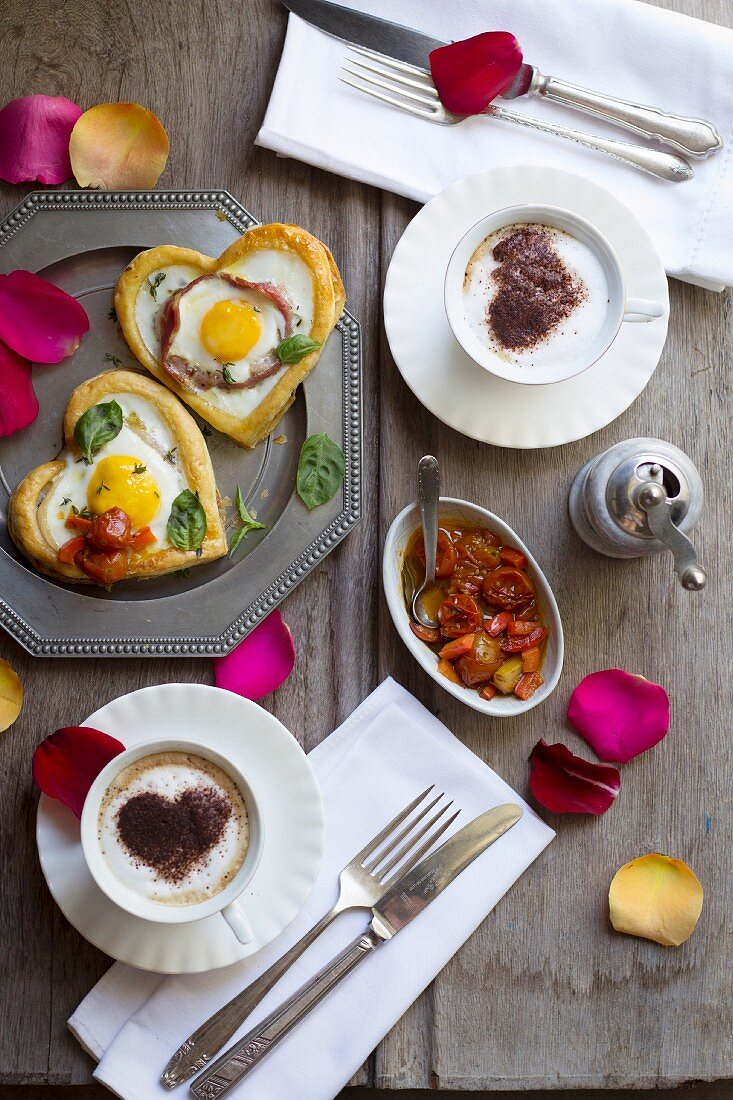 Puff pastry hearts with egg and bacon served with braised cherry tomatoes and cappuccino with a cocoa heart
