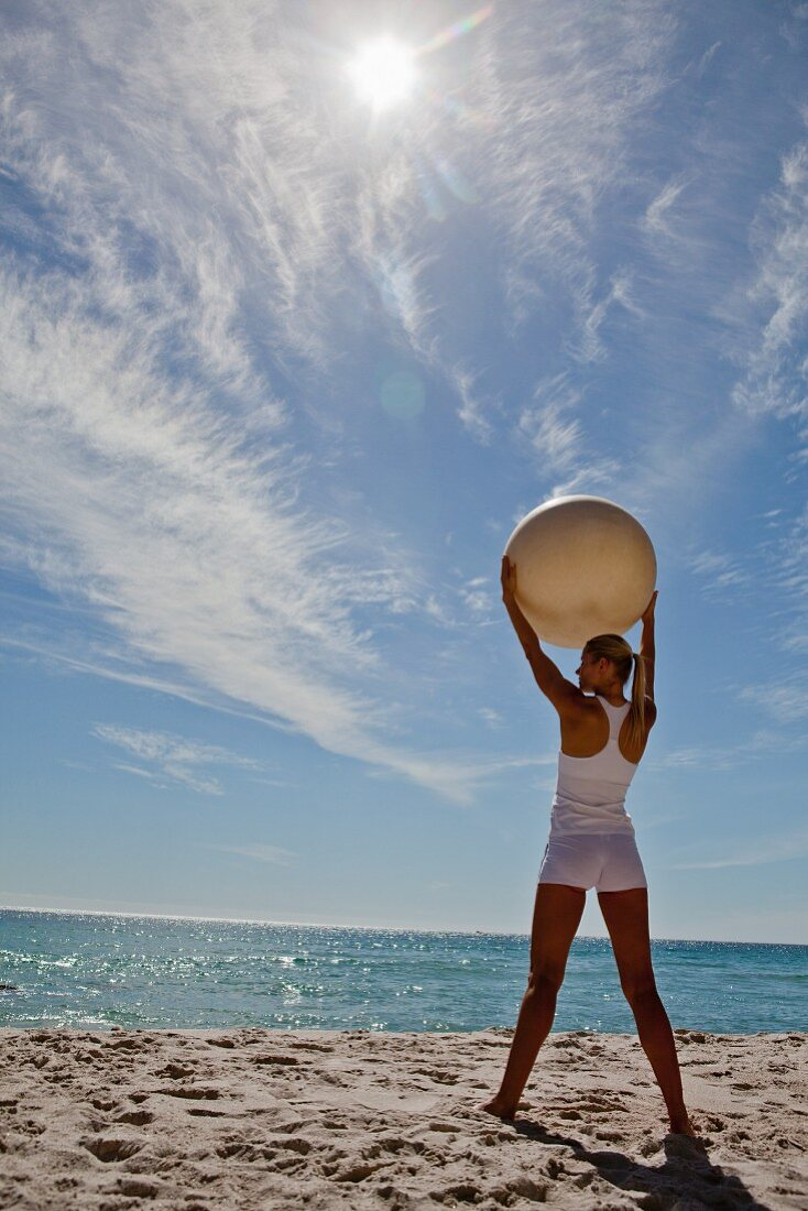 A woman on a beach doing yoga stretching with an exercise ball