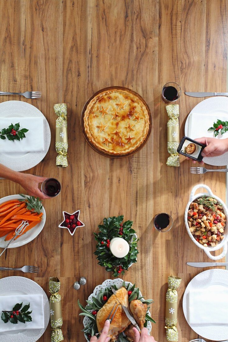 A table laid for Christmas dinner with a roast, sides and pie