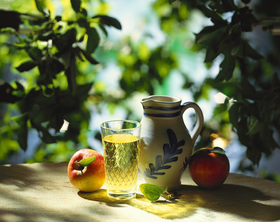 Cider still life with stone jug on a garden table