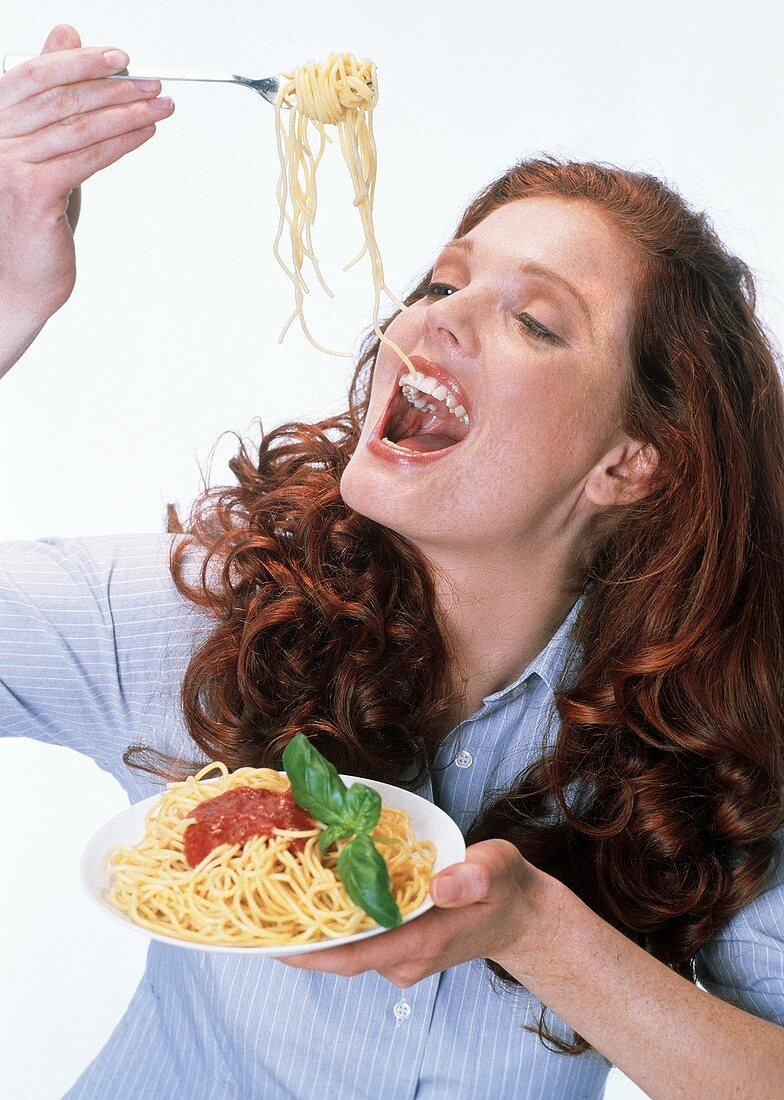 Red-haired woman eating spaghetti with tomato sauce