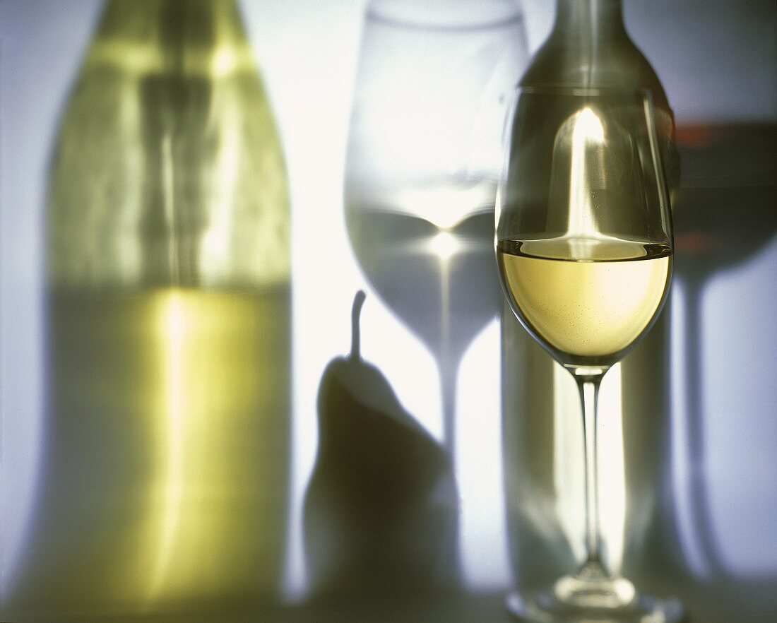 Glass of White Wine with Reflected Bottle