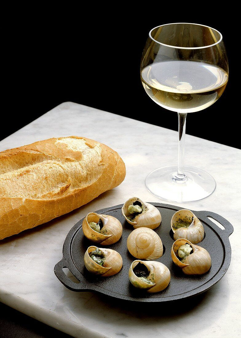 Snail with Herb Butter in cast iron Pan with Loaf of French Bread and Glass of White Wine