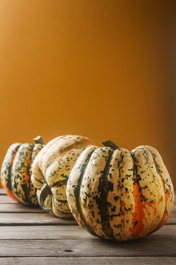 An arrangement of three pumpkins against an orange background