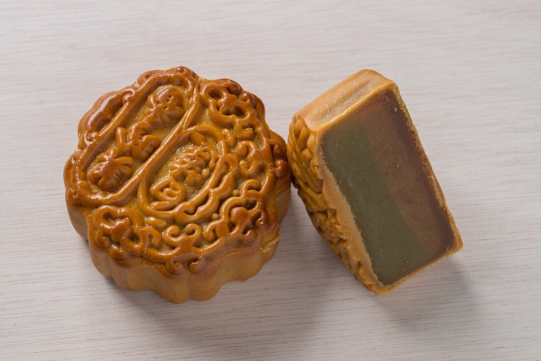Two Chinese mooncakes, one whole and one cut in half