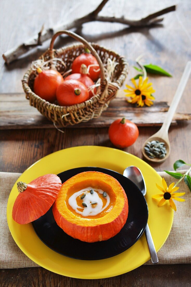 Pumpkin soup served in a hokkaido pumpkin with a basket full of small pumpkins and flowers in the background