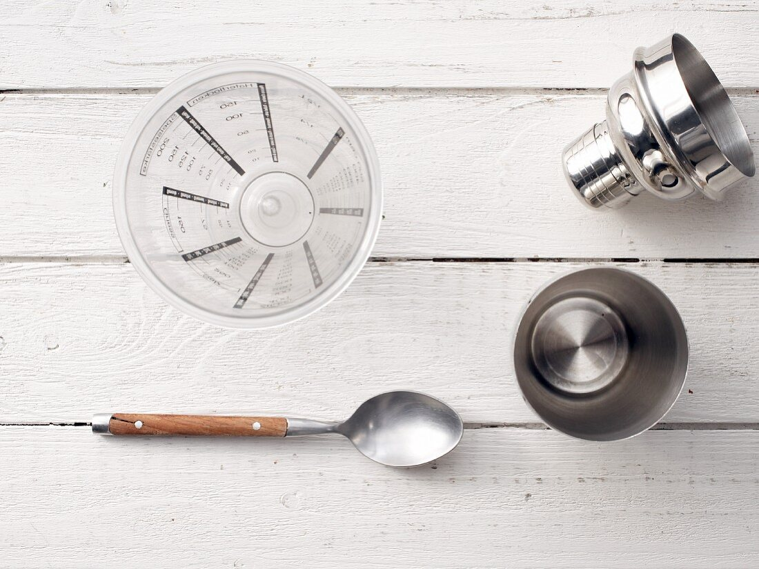 A cocktail shaker, spoon and measuring jug