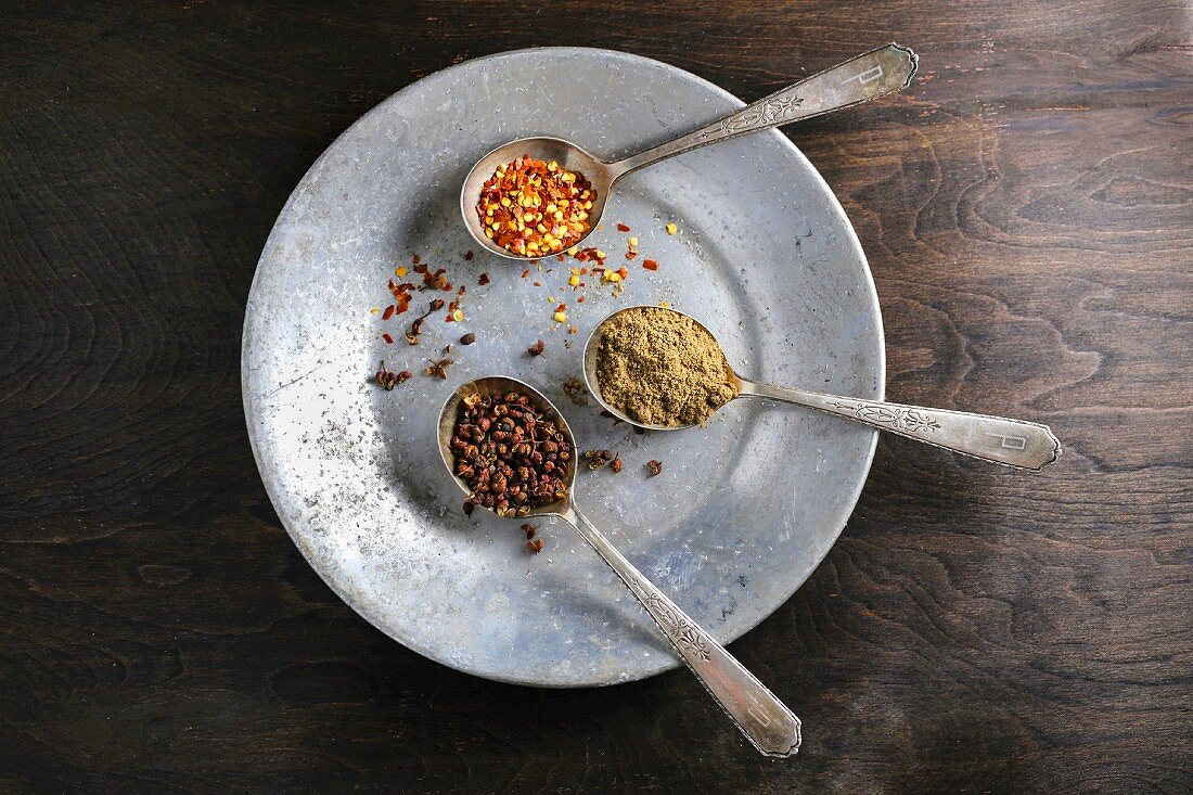 Three spoons containing spices on a metal plate