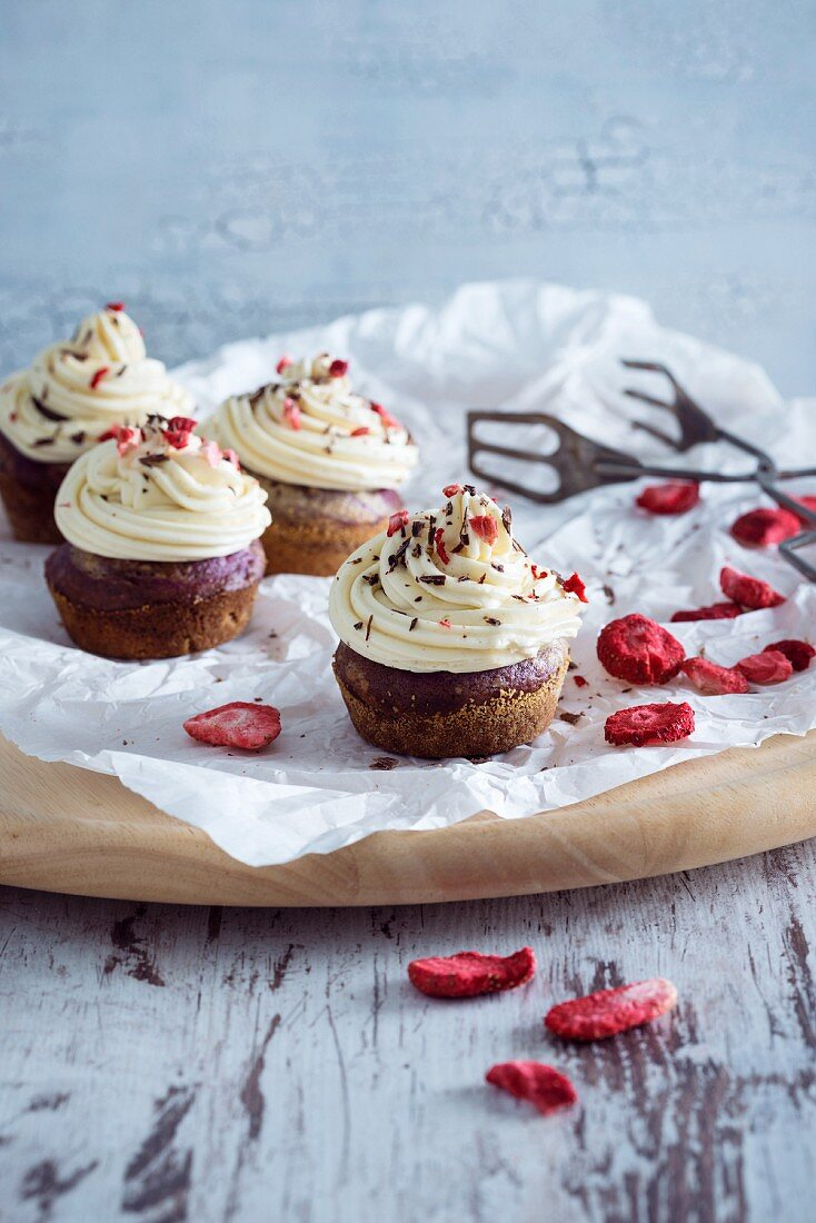 Vegan chocolate cupcakes with vanilla frosting and freeze-dried strawberries
