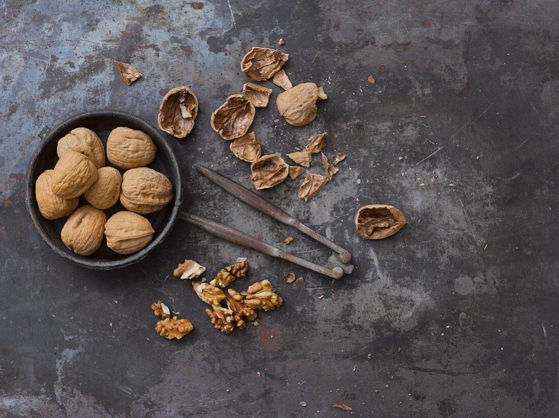 Whole walnuts, nut shells, a nutcracker and walnut seeds