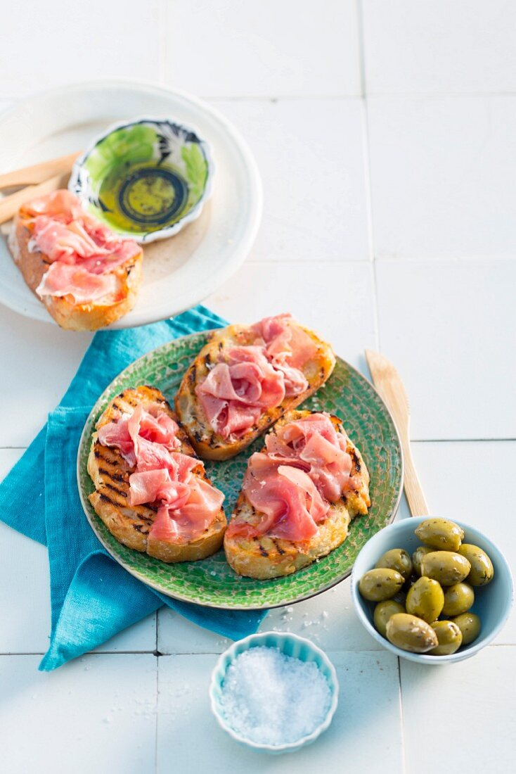 Grilled tomato bread with serrano ham and green olives