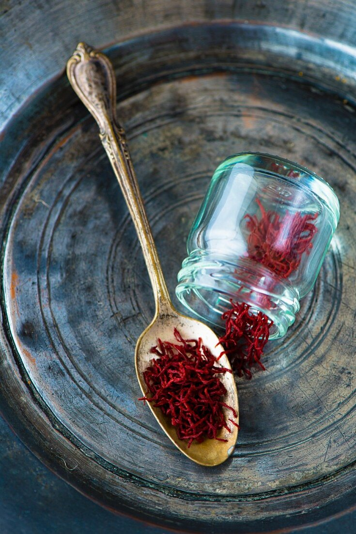 Persian saffron threads on an antique spoon and in a glass jar on a tin plate