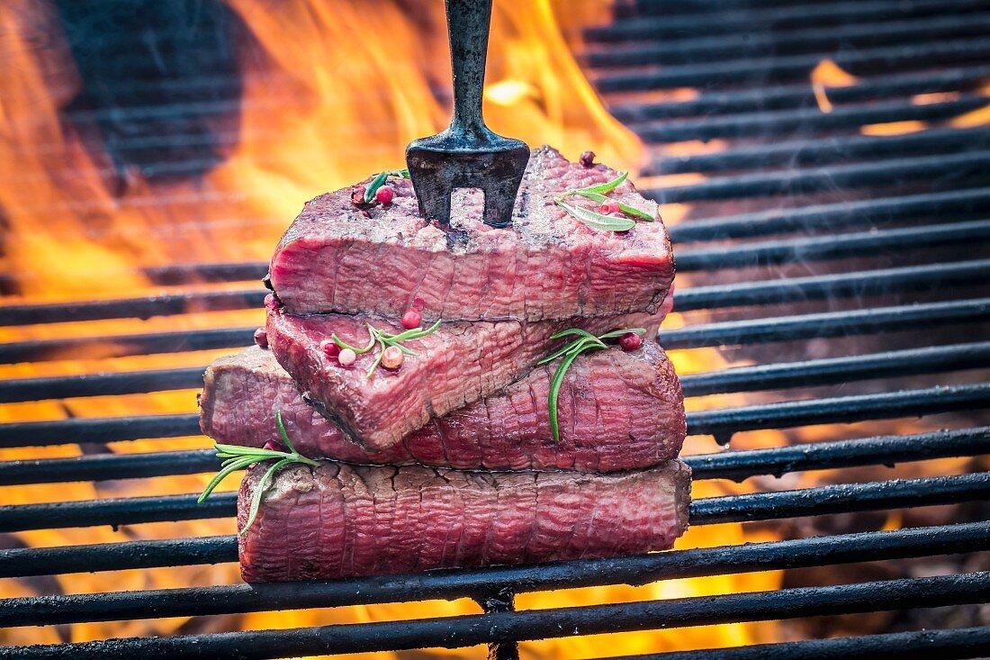 Steaks auf Fleischgabel auf dem Grill mit Rosmarin und Pfeffer