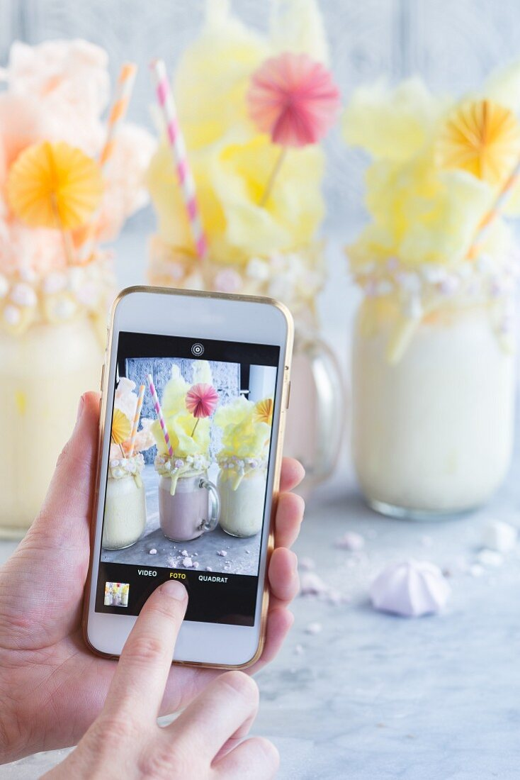 A blogger taking a photograph of freak shakes with their mobile phone