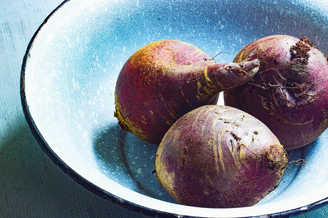 Three beetroot in an enamel bowl