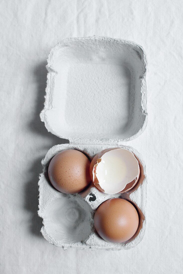 An egg box with whole eggs and eggshells