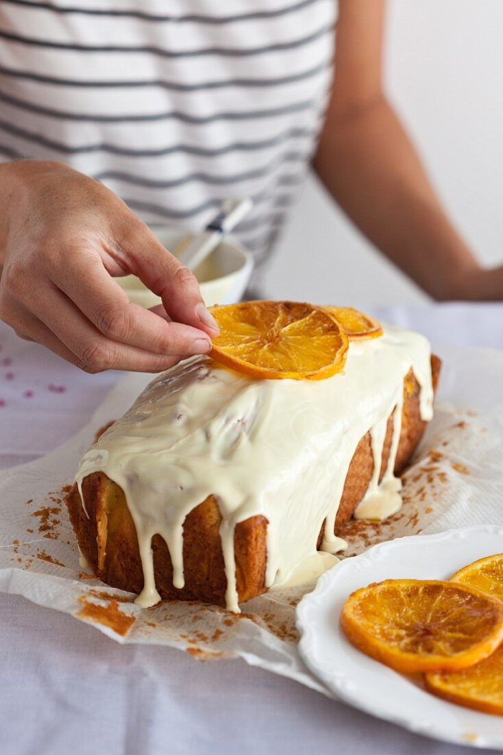Orange cake being decorated with candied orange slices