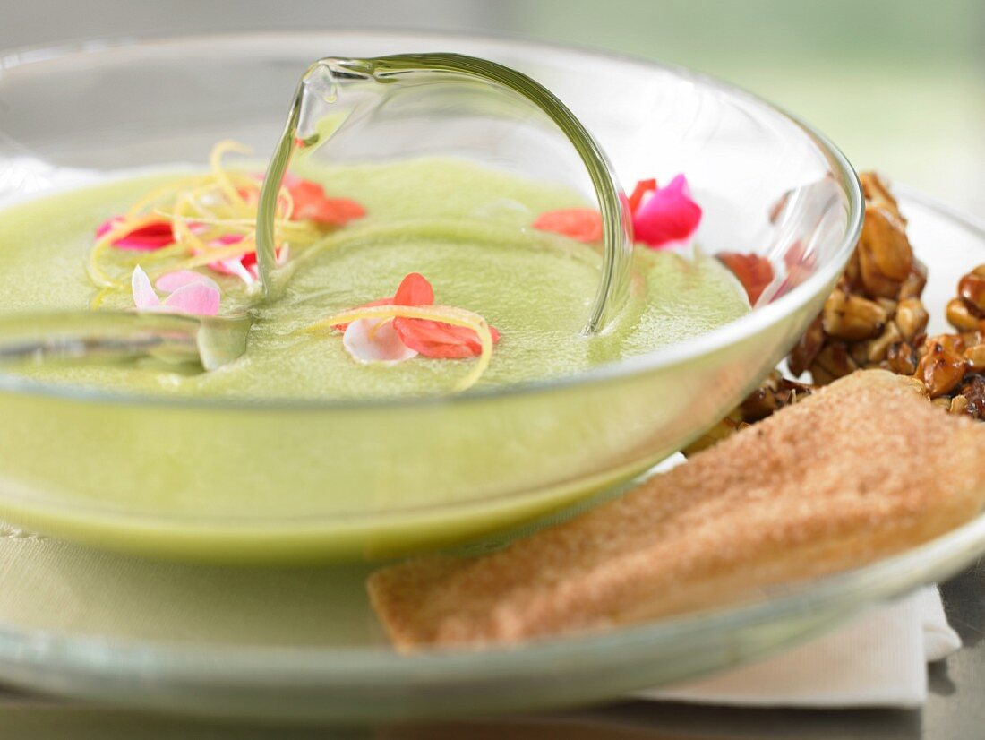 Cold green apple soup with nut brittle, crunchy biscuits, and edible flowers