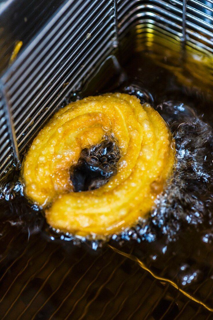A churro in a deep fat fryer with oil