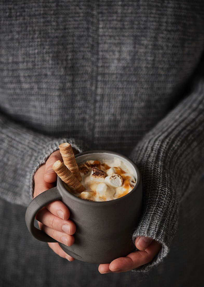 White hot chocolate with marshmallows, caramel sauce and wafer rolls
