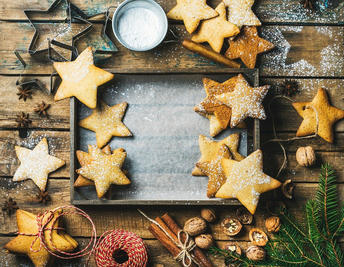 Gingerbread cookies, sugar powder, nuts, spices, baking molds, fir-tree branch and decorative rope