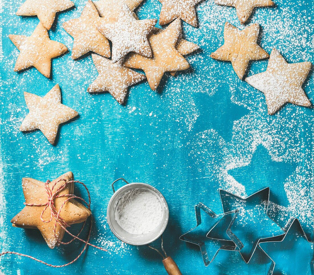 Sweet gingerbread cookies in shape of star with sugar powder on bright blue painted plywood background